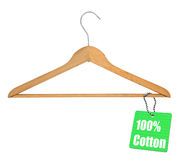 Coat hanger with cotton tag. Wooden coat hanger with 100% cotton tag, white studio background Stock Images