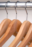 Coat Hangers. Empty Wooden Coat Hangers Hanging From A Storage Rail Stock Images