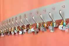 Coat hooks with labels organized in a row Stock Images