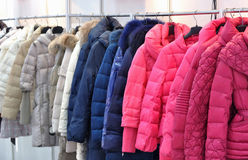 Coat and jacket for winter. Warmming coat and jacket in different colors, for winter, is hanging for sale Stock Photos