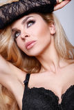 The coat portrait of a beautiful blond woman with green eyes in black sexy lingerie Stock Photos