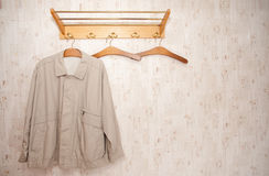 Coat rack. Indoor shot of an wooden coat rack and an old fashioned jacket on a coat hanger Stock Image