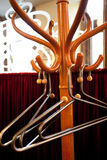 Coat rack. Wooden Coat rack with metal hangers in little French restaraunt Stock Photo