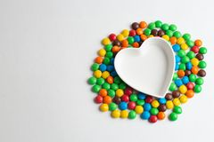 Coated chocolate candies shaped into a heart. Multicolor chocolate candies on the white background stock photo