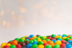 Coated chocolate multicolor candies on the white background with bokeh lights. Coated chocolate multicolor candies on the white background with bokeh yellow stock images