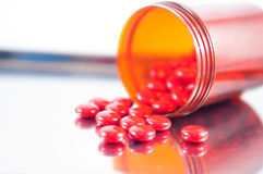 Coated red tablet and brown bottle on dispensing tray Stock Image