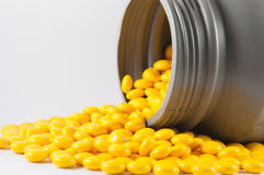 Coated yellow tablet and gray plastic bottle on white royalty free stock photography