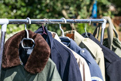 Coats and jackets on rack at thrift store to resale. Women and men coats and jackets on rack display at garage sale or thrift store to resale, reuse, recycle or stock images