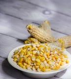 Cob i żółci kukurydzani nasiona w białej szklanej wazie na białym drewnianym tła zea Maj zdjęcie royalty free