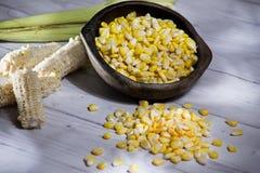 Cob i kolor żółty kukurydzane adra w glinianym garnku na białym drewnianym tła zea Maj fotografia stock