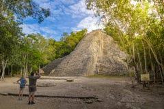 COBA MEXICO - FEBRUARI 3, 2016: Turister på fördärvar av den forntida Mayan staden Coba håller ögonen på pyramiden och tar bilder Arkivbild