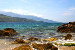 Cobalt blue Aegean sea and mountains. Samos, Greece. View of the coast of the Greek island of Samos. A view of the Aegean sea, mountains and rocks Royalty Free Stock Photos