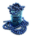 Cobalt blue freshwater pearls in drinking glass. Strands of cobalt blue freshwater pearls overlapping in a blue glass drinking cup Stock Photos