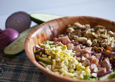 Cobb Salad. Generous helping of Cobb Salad served in wooden bowl surrounded by fresh vegetables, placed on a blue plaid place-mat stock images