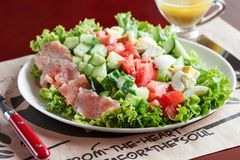 Cobb salad - traditional american food. Hearty meal of salmon, eggs, cucumber, avocado and lettuce leaves with mustard dressing stock images