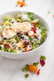 Cobb Salad on white. Fresh organic Cobb salad topped with homemade Ranch dressing, hard boiled eggs, bacon, peppers, peas, and green onions on white wood stock photography