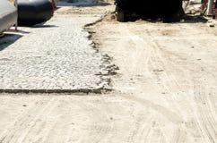 Cobble la piedra de pavimentación en la mitad de la calle en el sitio de la reconstrucción de la ciudad fotografía de archivo