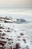 Cobble la playa de piedra del mar leído en puesta del sol foto de archivo libre de regalías