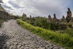 Cobble la strada per scavare la casa dei camini che leggiadramente le rocce si espandono rapidamente in Pasabag, la valle dei mon fotografie stock
