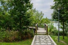 Cobble la trayectoria en el extremo de la pasarela cercada orilla del lago en summe nublado foto de archivo libre de regalías