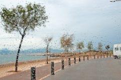 Cobble los árboles y las gotas de agua de piedra del océano de la calle en la ventanilla del coche foto de archivo