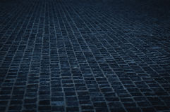 Cobble stone pavement street in an urban night - cobblestone pattern with blue color tone Royalty Free Stock Photo