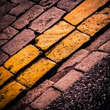 Cobble stone road. Abstract background of cobble stone road with two yellow rows royalty free stock images