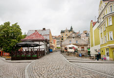 Cobble stones of the old street with tiny shops Stock Photos