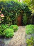 Cobble weg aan de geheime tuineningang van overhangende wijnstokken en een oude rustieke deur stock foto's