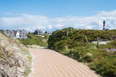 Cobbled footpath through dunes on the island of Sylt, Germany, with typical red and white lighthouse and buildings in background Stock Photography