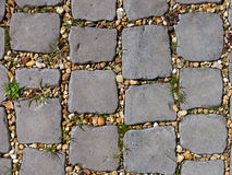 Cobbled path. Weathered cobbled path with golden gravel and weeds between the stones royalty free stock photo
