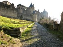 Cobbled path approaching the old walled city of Carcassonne, France. Cobbled path with two people approaching the old walled city of Carcassonne, France stock photos