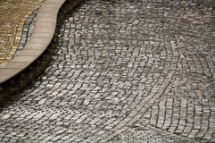 Cobbled pavement. A curved pavement or road surfaced with rough gray cobble stones stock images