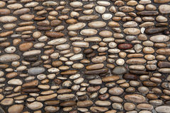 Cobbled pavement made of river rounded pebbles. Background textu Royalty Free Stock Images