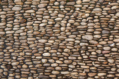 Cobbled pavement made of river rounded pebbles. Background textu Royalty Free Stock Image