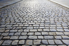 Cobbled Road. Cobbled stone road shown at a small angle, reflection of light seen on the road Royalty Free Stock Photography