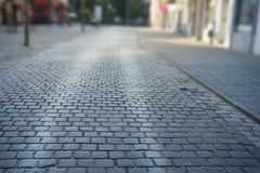 Cobbled stone road early morning with reflection of light. Stock Photo