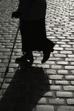 Cobbled street. Old woman silhouette crossing a cobbled street stock photo