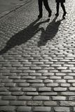 Cobbled street. Pedestrian silhouettes crossing a cobbled street royalty free stock images