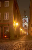 Cobbled street and church tower at night Stock Photo