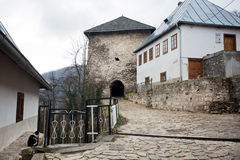 Cobbled street with historic fortress. Cobbled street with stone tower of historic fortress of 14 century in the Bosnian city Jajce in Bosnia and Herzegovina Stock Photos