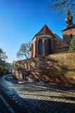 A cobbled street, a medieval wall and a gothic church Royalty Free Stock Photo