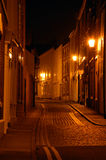 Cobbled Street At Night. Old cobbled street at night showing town houses and street lamps Royalty Free Stock Photo