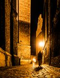 Cobbled street of Old Town with dark blurred silhouette of person. Evokes Jack the Ripper.  Royalty Free Stock Photo