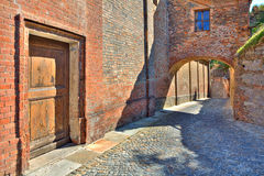 Cobbled street and red brick wall in italian town. Stock Image