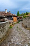 Cobbled street and rustic houses in Zheravna, Bulgaria. Zheravna, Bulgaria - architectural reserve of rustic houses and narrow cobbled streets from the Bulgarian royalty free stock image