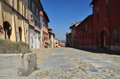 Cobbled street in the Saluzzo old town area. Piemonte, Italy. Old city of Saluzzo, province of Cuneo, Piedmont - Piemonte - Italy. Pedestrian street and flowered royalty free stock photos
