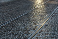 Cobbled street with tram rails. In winter, with sunlight Stock Photos