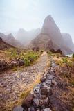 Cobbled Wanderweg zu Ponta tun Solenoid über erstaunlichem trockenem Aranhas-Tal mit enormen Bergspitze- und Hausruinen Santo Lizenzfreie Stockfotografie