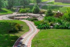 Cobbledweg in het park en de decoratieve vijver Het Concept van het landschapsontwerp Stock Foto's